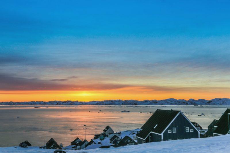 夕暮れのヌーク フィヨルドに沈む夕日とイヌイットの人々の家々